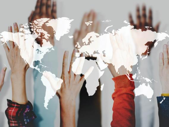 Hands raised with a global transparent map in foreground