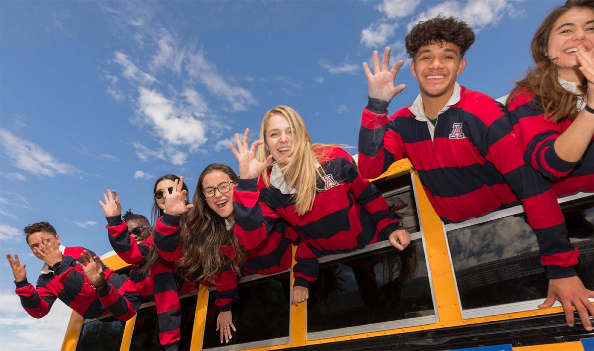 Photo of students waving from bus